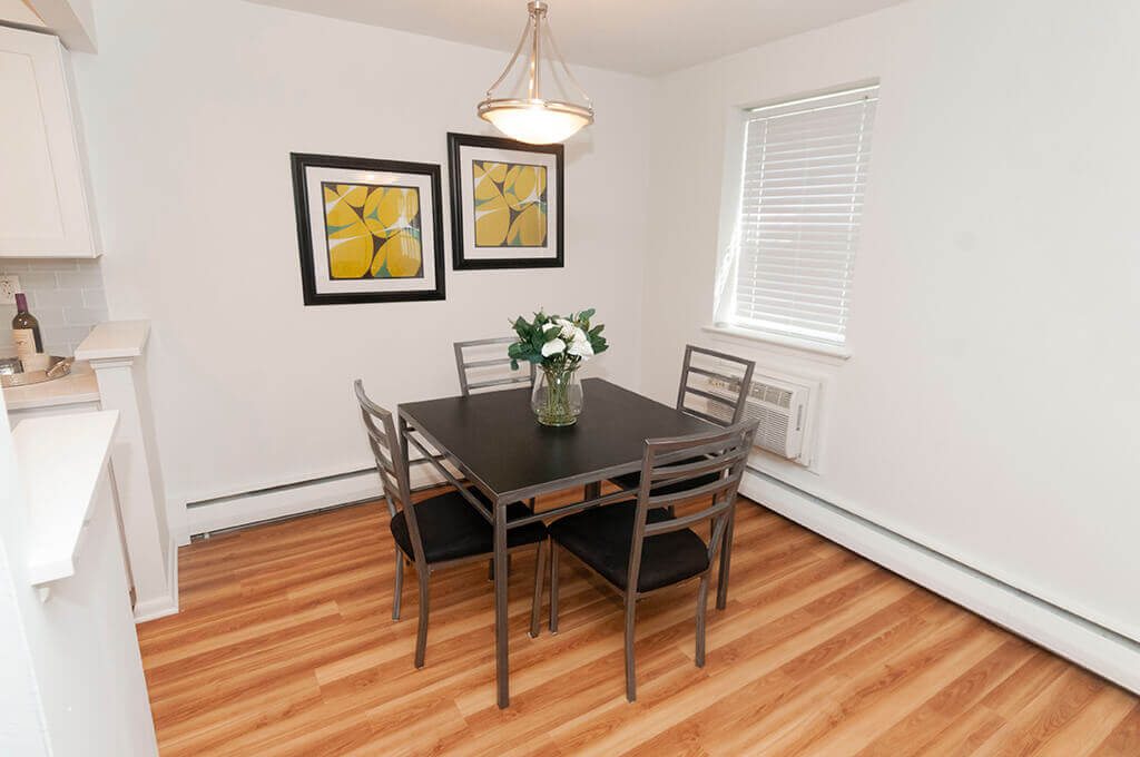 Dining room table nook with yellow pictures above